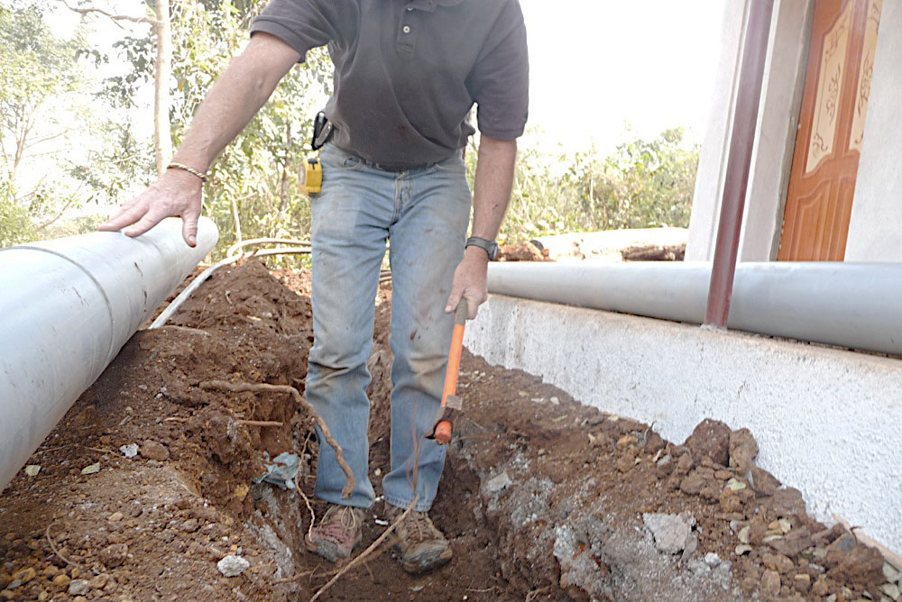 Worker in a ditch with three metal astrological bangle on right wrist