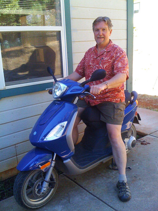 Kent Williams on scooter wearing three metal bangle on left wrist
